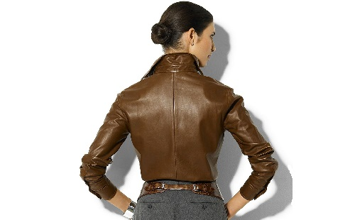 Girl in a brown leather jacket stands back to the viewer