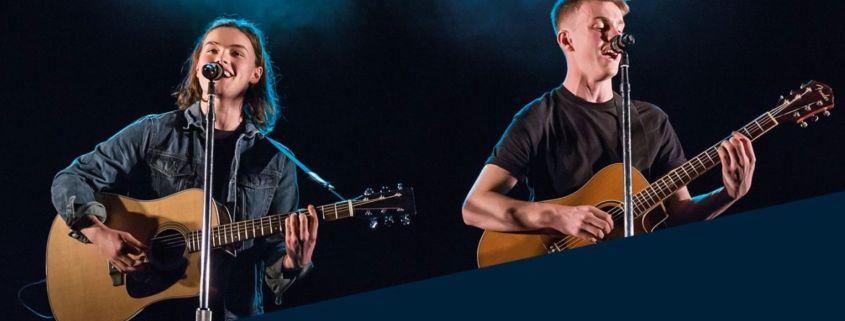 2 ArtsEd students singing with guitars