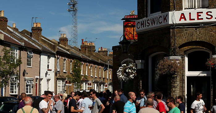 Fans enjoy a drink outside a pub near Griffin Park stadium before the match