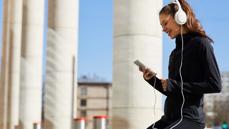 Cheerful excited young female jogger in track suit sitting on concrete slab and using smartphone while chatting online and listening to music in headphones during rest