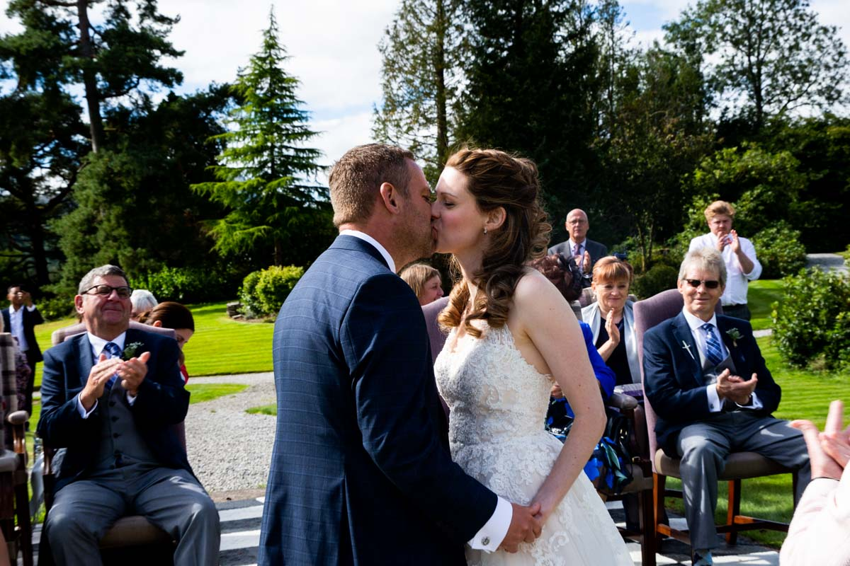 Outdoor wedding ceremony kiss at MacDonald Forest Hills Hotel & Spa