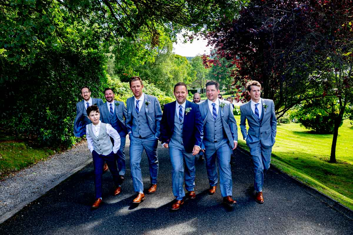 Groom and ushers on the walk to the wedding ceremony at MacDonald Forest Hills Hotel