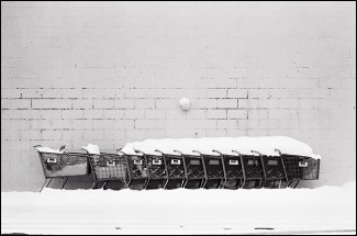 A line of carts sit beside the Big Lots store in New Haven, Indiana. They are covered in heavy snow after a winter storm.