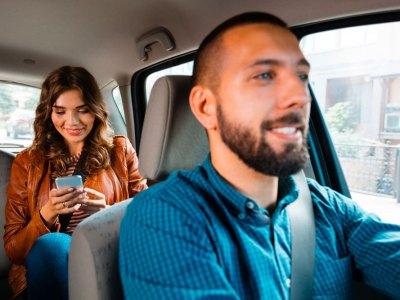 Socio conductor de Uber junto a una pasajera