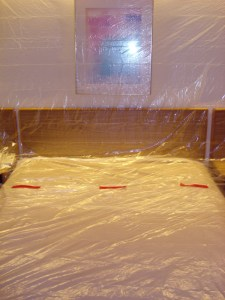 Hotel room bed (and headboard and side tables) covered in clear plastic
