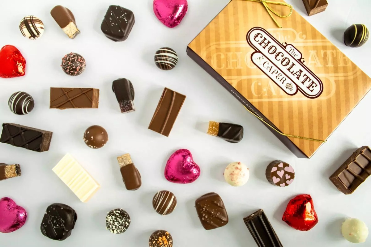 a variety of candies laid out on a white background - including truffles, pralines, caramels and more - with a Chocolate Caper box in the corner