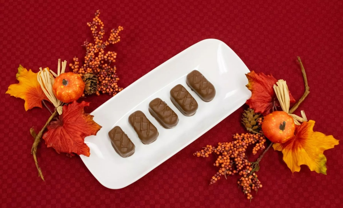 caramel apple gels - apple cider gels wrapped in caramel and dipped in milk chocolate - laid out on a tray