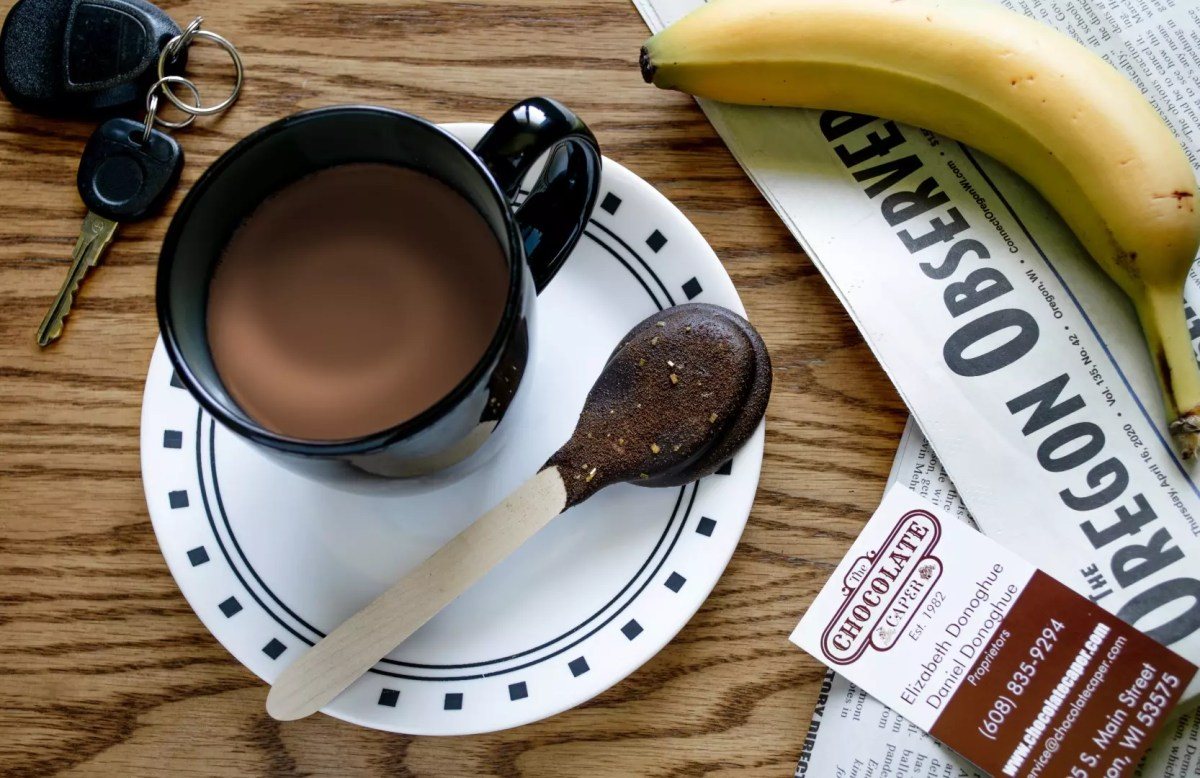 A chocolate dipped spoon on a plate with a mug of hot chocolate, all sitting on a table with an Oregon Observer newspaper, Chocolate Caper business card, banana and keys