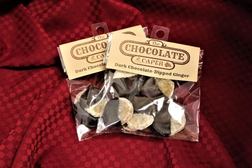 Two bags filled with discs of dark-chocolate dipped candied ginger on a red background