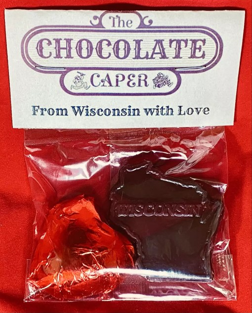 "A dark chocolate ""From Wisconsin with Love"" containing a dark chocolate heart wrapped in red foil and a solid dark chocolate shaped like the state of Wisconsin."