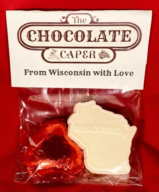 "A white chocolate ""From Wisconsin with Love"" containing a dark chocolate heart wrapped in red foil and a solid dark chocolate shaped like the state of Wisconsin."