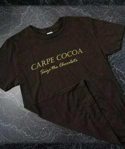 "A brown t-shirt with the words ""Carpe Cocoa - Seize the Chocolate"" in gold on the front."