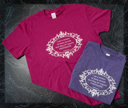 """Heathered pink and heathered purple t-shirts with the words """"I am a woman of many moods, and they all require chocolate"""" in white on the front."""