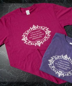 "Heathered pink and heathered purple t-shirts with the words ""I am a woman of many moods, and they all require chocolate"" in white on the front."