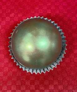 A milk chocolate magic drinking chocolate orb that is decorated in green luster dust, in a cup on a red background.