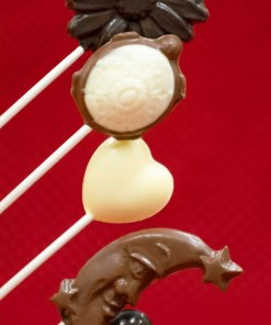 A flower, turtle, heart and crescent moon lollipops stacked in various chocolates