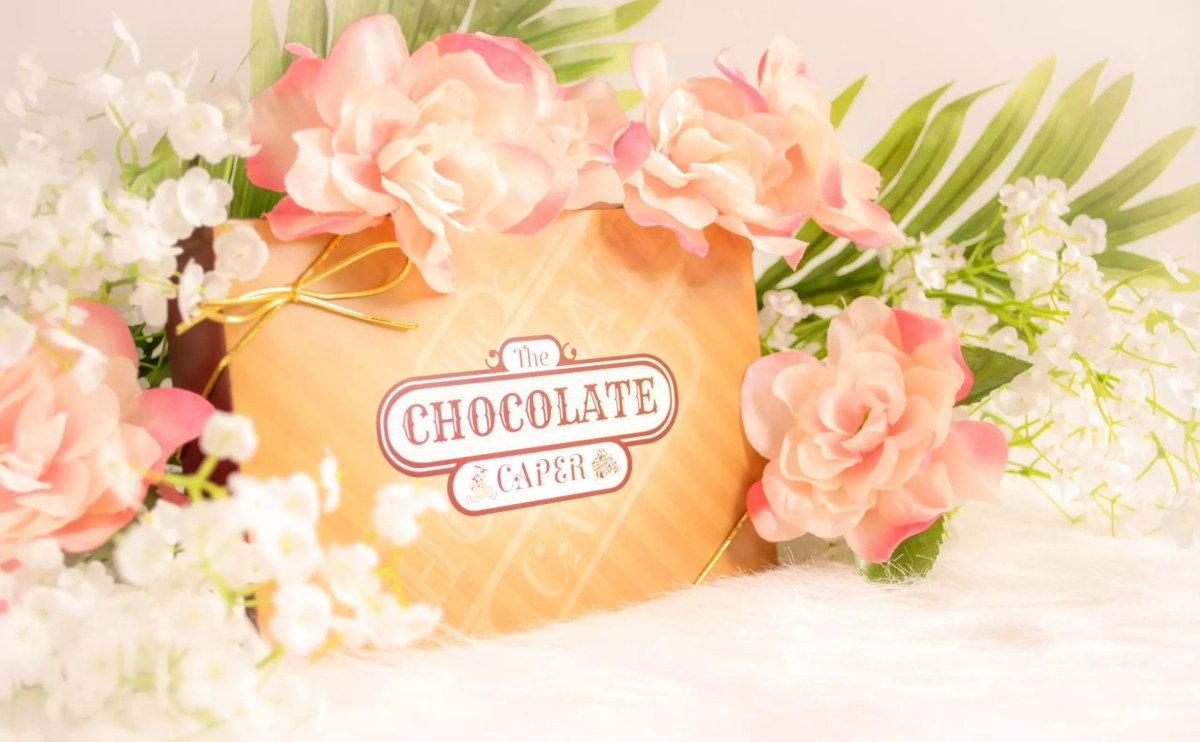 A Chocolate Caper box lid with flowers laid around it.