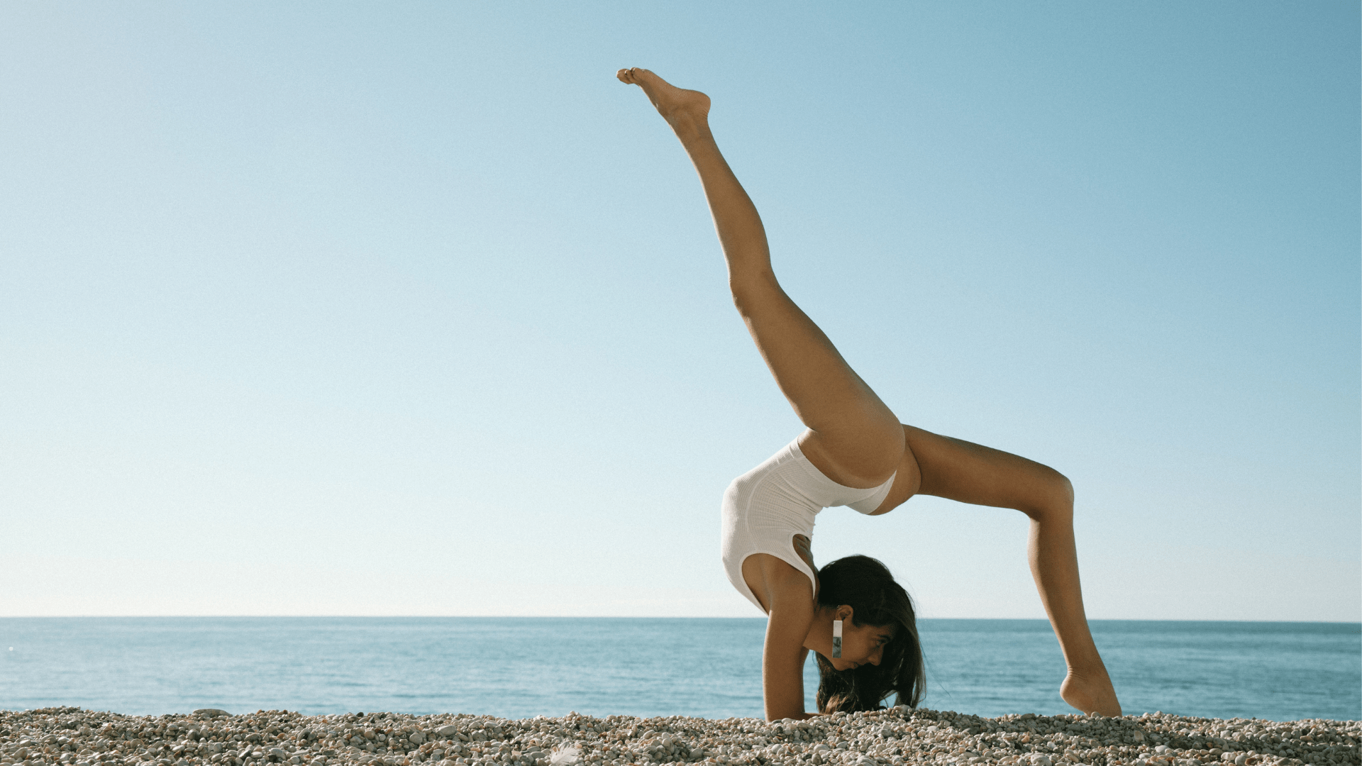 body contorsion yoga pose in front of the ocean with plaque long and lightweight earring