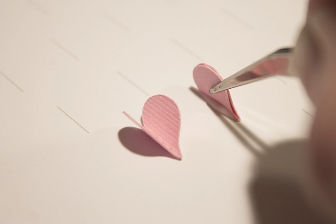 held the folded hearts with tweezers