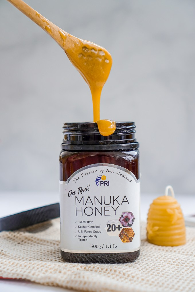 manuka honey dripping from a spoon.