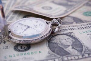 A clock lying on a pile of dollar bills.