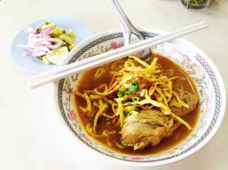 Khao soi - the northern Thai dish of noodles in a spicy curry soup - is one of my favorite dishes in the world. The first thing I did when I landed in Chiang Mai was visit an old haunt, a little street side restaurant with a cart of hanging chickens that sells the specialty. Unlike the versions I get in the US, they serve it here with a tender chicken leg. Not boneless and skinless.