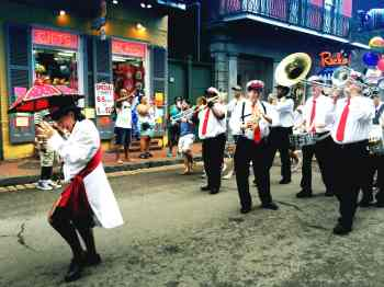 A band marches down Bourbon Street in New Orleans.