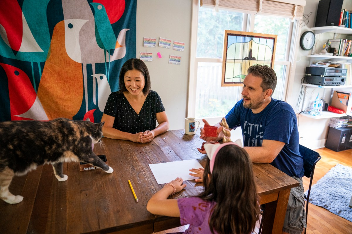 JC Sanford and Asuka Kakitani are interrupted by their cat Sora while spending time with their daughter playing a card game at home in Northfield.