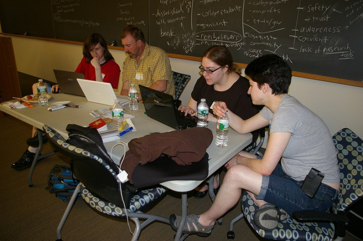 Sam and Julia working on content while Daniel and Matt talk in the background