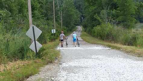 James (right) and Me walking our bikes through a section of road with large stones. Photo courtesy of Andy