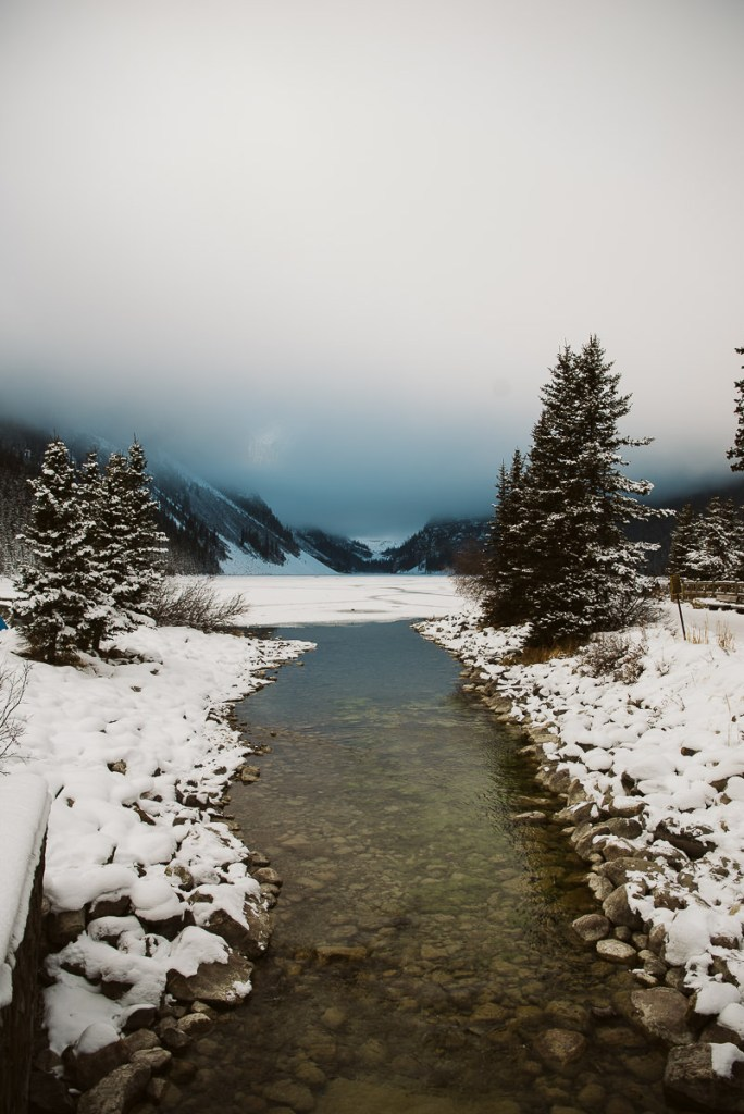 Looking down the open waterway of a semi-frozen Lake Louise in November sitting under low hanging clouds covering the mountains.