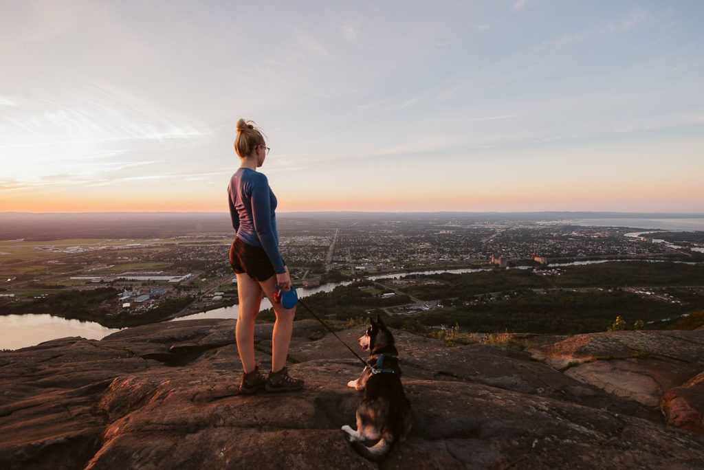 Young girl and her husky standing on the top of Mount McKay in Thunder Bay as the sunsets.