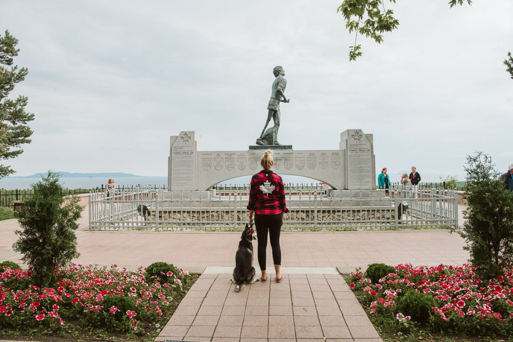 Young blonde woman and her husky looking at the Terry Fox memorial.