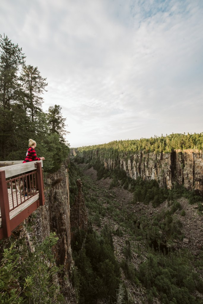 Blonde girl looks out over the viewing platform to the north of the Ouimet Canyon.