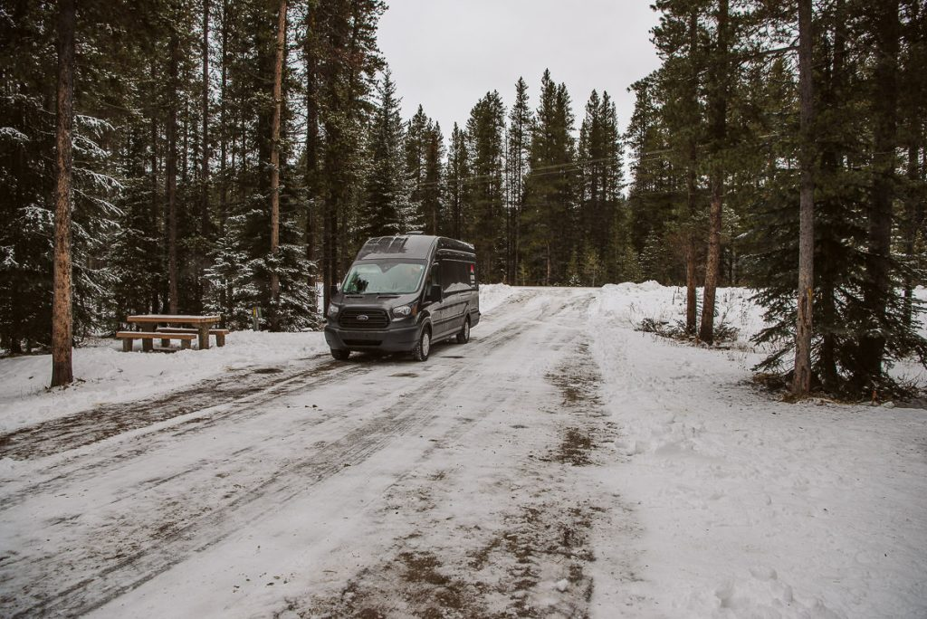 Campervan parked in one of the campsites at Lake Louise Campground in November after a snowfall.