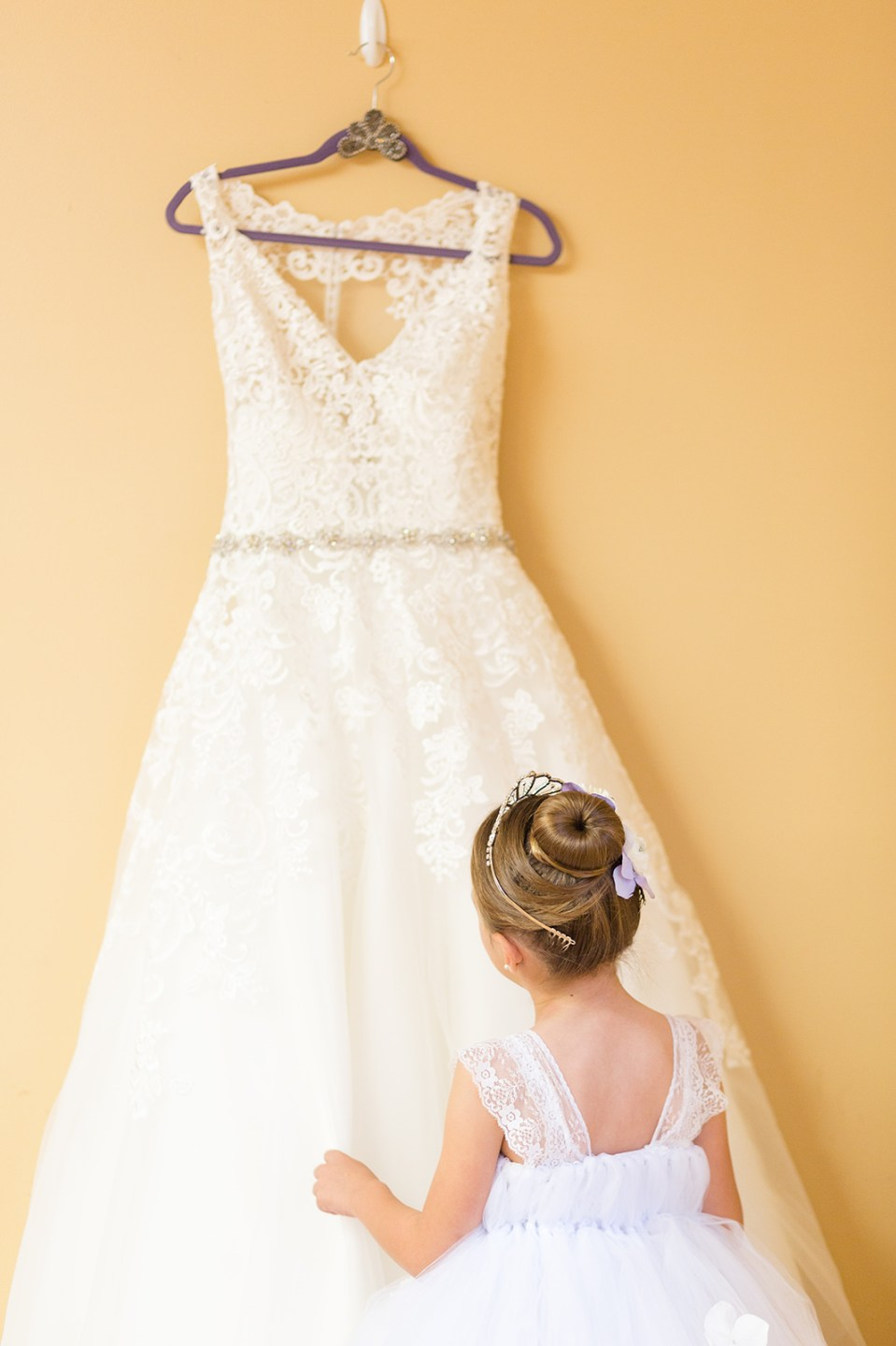flower girl looking at wedding dress hung up