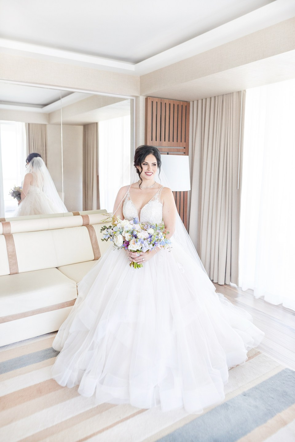 Bride in a white ballgown holding a bouquet in the bridal suite at her Conrad Fort Lauderdale Beach wedding