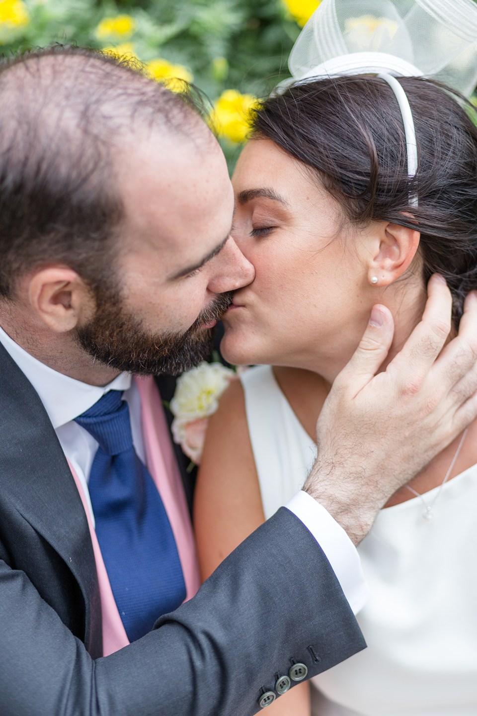 bride and groom kissing while his hand is on her cheek