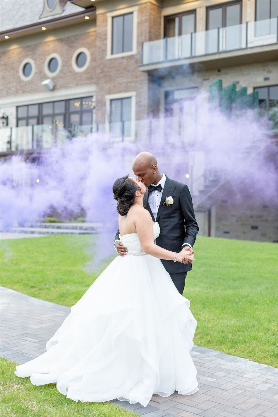 couple holding each other as purple smoke fills the air