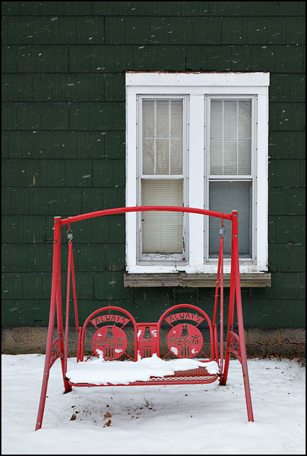 CocaCola porch swing in front of an old house in a