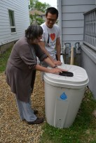 Chris and Lida placing her rain barrel