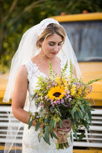 Bride posing in front of an old yellow truck.