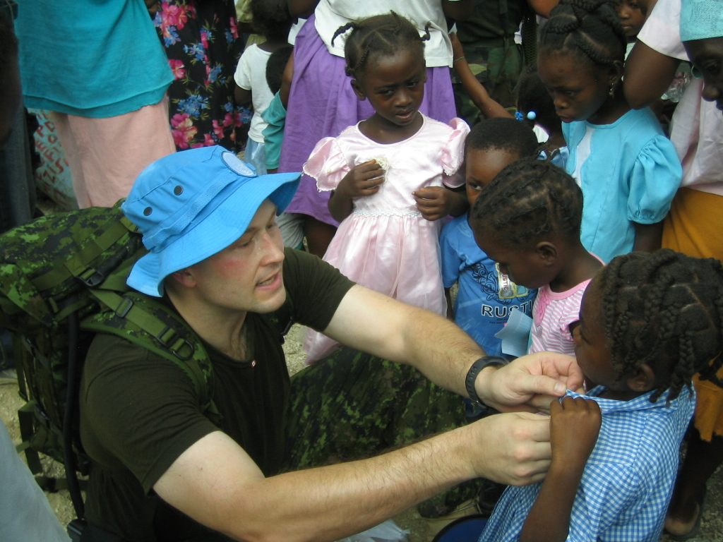 Chris putting on Canadian Flag pins at the Pikas School, in the mountains of Haiti (undated 2009 photo)