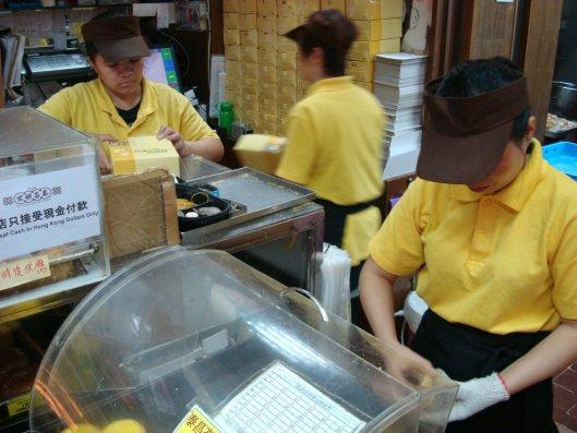 泰昌餅家的店員忙碌但熟練的倒出蛋塔並裝盒