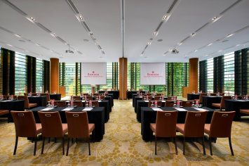 Interior Photography of the Ramada at Zhongshan Park Singapore meeting room in a classroom setup with hotel logo on projector screens