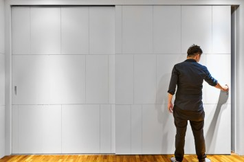 Interior design photography showing man closing office door at simei rise condo in singapore