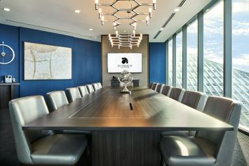 Interior Photography of the sky premium boardroom in Singapore looking down the table to a tv with sky premium logo