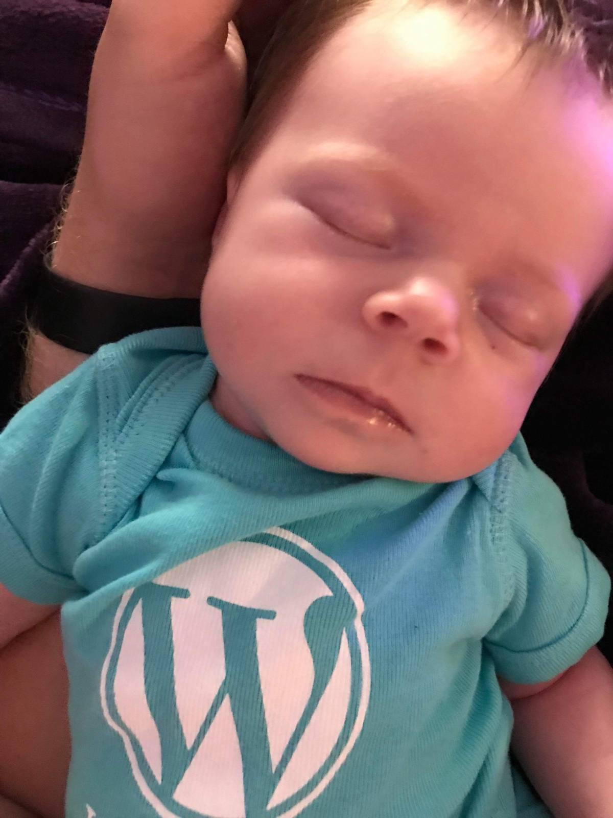 Sleeping baby wearing a WordPress shirt.