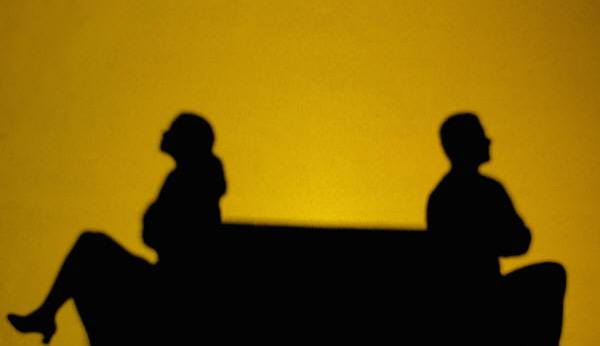 silhouettes of woman and man back to back with arms crossed