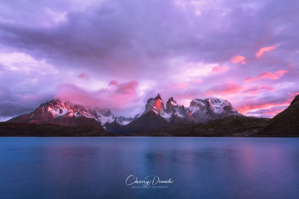 Cuernos del Paine  standing tall among the wind as the sunrise sets the clouds ablaze in Torres Del Paine National Park